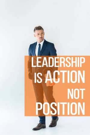 """Photo for Handsome businessman standing with laptop and looking away isolated on white with """"leadership is action, not position"""" lettering - Royalty Free Image"""