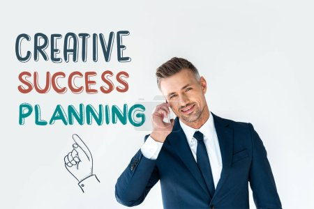 Photo for Smiling handsome businessman talking by smartphone and looking at camera isolated on white with creative success planning - Royalty Free Image
