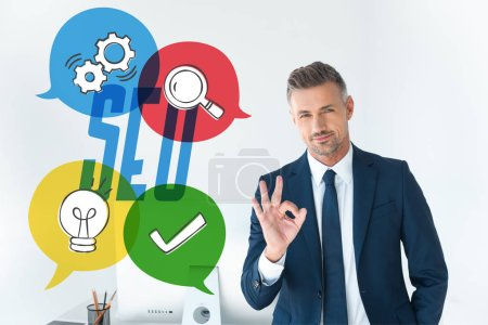 Photo for Handsome businessman showing okay gesture and looking at camera isolated on white with seo icons - Royalty Free Image