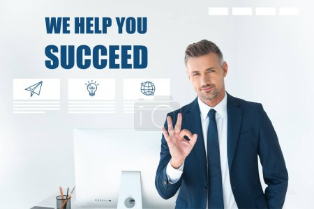 "Photo for Handsome businessman showing okay gesture and looking at camera isolated on white with ""we help you succeed"" lettering - Royalty Free Image"