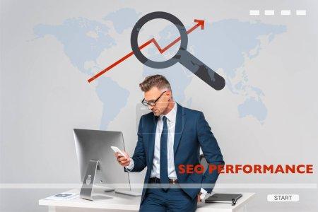 Photo pour Bel homme d'affaires appuyé sur la table et utilisant smartphone isolé sur gris avec carte du monde et performance SEO - image libre de droit