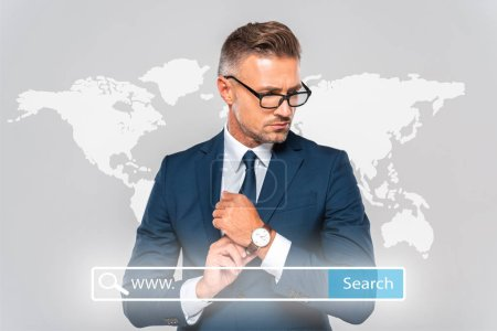 Photo for Handsome businessman wearing wristwatch and looking away isolated on grey with world map and search bar - Royalty Free Image