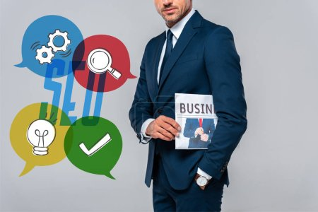 Photo for Cropped image of businessman holding newspaper isolated on grey with seo icons - Royalty Free Image