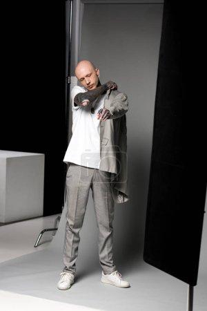 Foto de Vista integral de seguros de hombre tatuado con traje de chaqueta en estudio - Imagen libre de derechos
