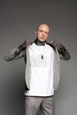 Photo for Stylish bald tattooed man wearing suit jacket and looking at camera on grey - Royalty Free Image