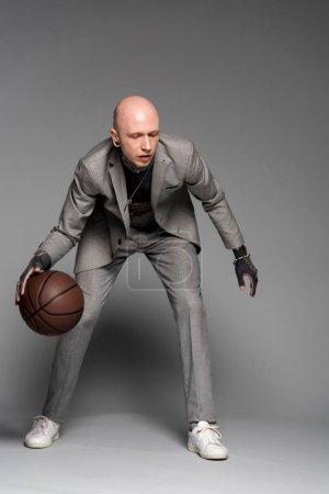 Foto de Vista de la longitud total de elegante hombre tatuado en juego jugando baloncesto en gris - Imagen libre de derechos