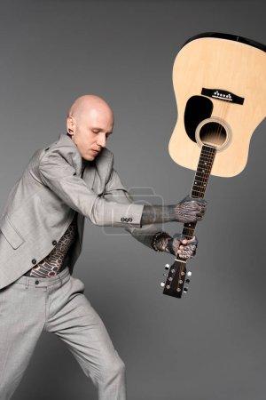 Foto de Hombre tatuado enojado en juego golpear guitarra acústica aislada en gris - Imagen libre de derechos