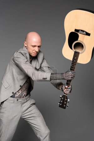 Photo for Aggressive tattooed man in suit hitting acoustic guitar isolated on grey - Royalty Free Image