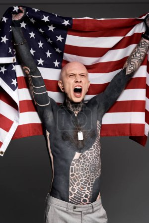 excited shirtless bare-chested man with tattoos holding american flag and screaming isolated on grey