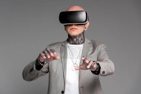 Foto de Con estilo hombre tatuado con casco de realidad virtual aislado en gris - Imagen libre de derechos