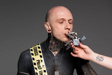 Photo pour Vue partielle d'une personne tenant un homme plus léger et tatoué avec une ligne transversale autour du corps fumant une cigarette roulante isolée sur du gris - image libre de droit