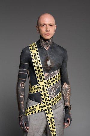 Photo pour Homme tatoué torse nu chauve avec ligne de police autour du corps regardant la caméra isolée sur gris - image libre de droit