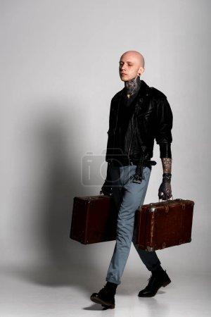 Foto de Hombre guapo tatuado en chaqueta de cuero que maletas y caminar en gris - Imagen libre de derechos