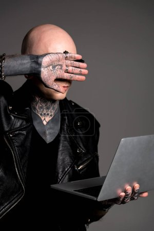 Foto de Hombre tatuado en chaqueta de cuero que laptop y ocultar rostro aislado en gris - Imagen libre de derechos
