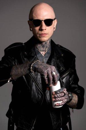 Foto de Calvo tatuado hombre chaqueta de cuero y gafas de sol apertura de soda puede aislado en gris - Imagen libre de derechos