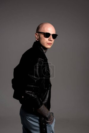 Photo for Side view of stylish tattooed guy in leather jacket and sunglasses standing isolated on grey - Royalty Free Image