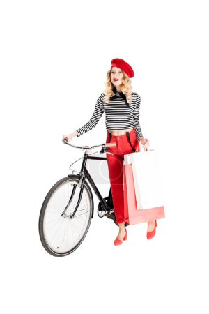 Photo for Happy woman holding shopping bags and smiling while standing near bicycle isolated on white - Royalty Free Image