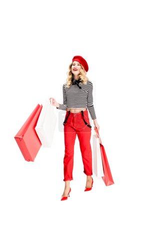 Photo pour Femme joyeuse debout avec des sacs à provisions isolés sur blanc - image libre de droit