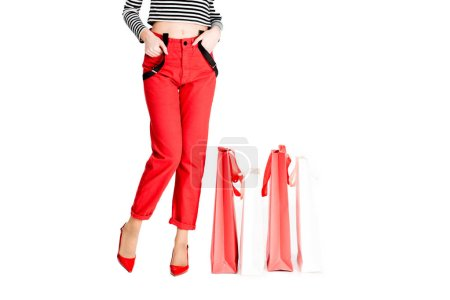 Photo for Cropped view of woman standing with hands in pockets near red shopping bags isolated on white - Royalty Free Image
