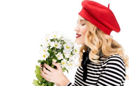 Photo pour Belle femme au béret rouge souriant tout en sentant les fleurs isolées sur blanc - image libre de droit