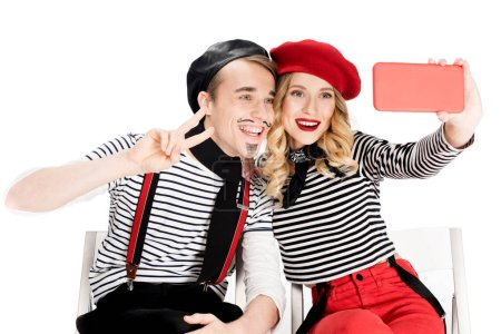 smiling french couple taking selfie on smartphone isolated on white