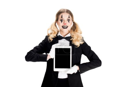 smiling blonde clown holding digital tablet with blank screen isolated on white