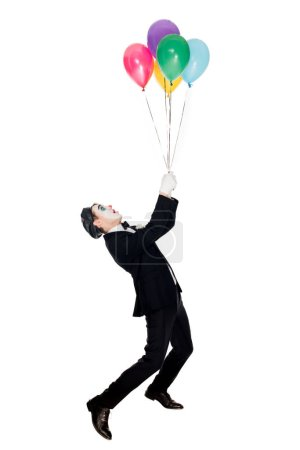 Photo for Clown in suit and black beret looking at helium balloons isolated on white - Royalty Free Image