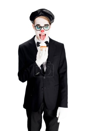 Photo for Crazy clown in suit showing tongue while eating cupcake isolated on white - Royalty Free Image
