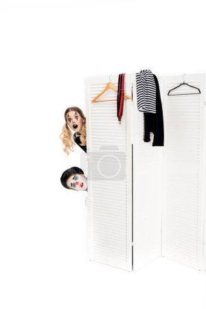 Photo pour Clowns surpris regardant par la porte du vestiaire isolé sur blanc - image libre de droit