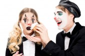 cheerful clown throwing cupcake in face of surprised woman isolated on white
