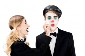 cheerful female clown throwing cupcake in face of surprised man isolated on white