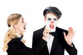 cheerful female clown throwing cupcake in face of dissatisfied man isolated on white