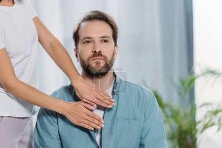 Photo pour Plan recadré de l'homme barbu assis et recevant un traitement reiki sur la poitrine - image libre de droit