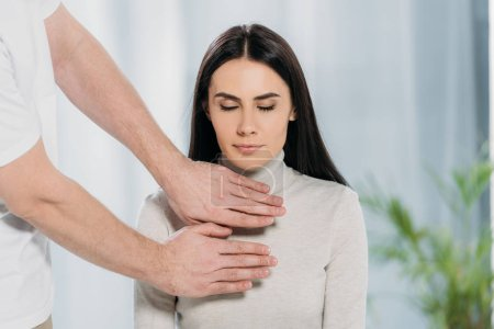 Photo for Cropped shot of young woman with closed eyes sitting and receiving reiki treatment on chest - Royalty Free Image
