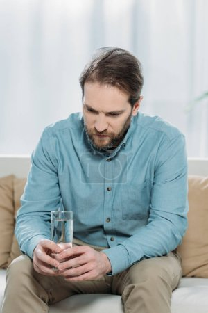 Photo for Upset bearded man holding glass of water and sitting on couch in psychotherapist office - Royalty Free Image