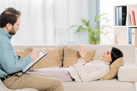 Photo for Side view of bearded psychotherapist writing on clipboard and young patient lying in couch - Royalty Free Image