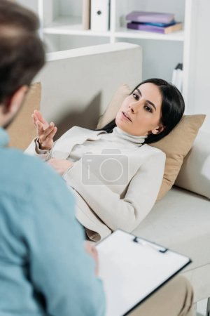 Photo for Young woman lying on couch and talking with professional psychotherapist - Royalty Free Image