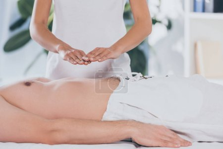 Photo for Cropped shot of bare-chested man receiving reiki healing treatment above stomach - Royalty Free Image