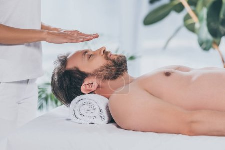 Photo for Cropped shot of bearded man with closed eyes lying and receiving reiki therapy above head - Royalty Free Image
