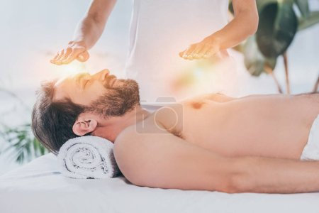 Photo for Calm bearded man with closed eyes lying and receiving reiki treatment on head and chest - Royalty Free Image