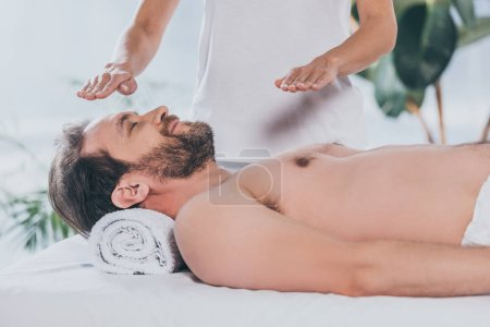 Photo for Calm bearded man with closed eyes lying and receiving reiki treatment - Royalty Free Image