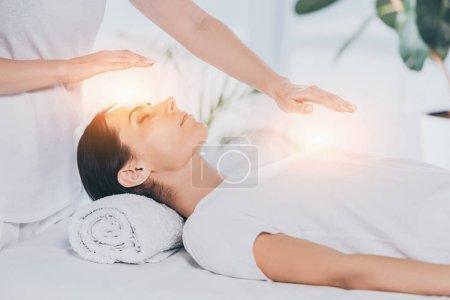 Photo pour Recadrée tir de guérisseur reiki fait séance de thérapie pour calmer la jeune femme avec des yeux fermés - image libre de droit