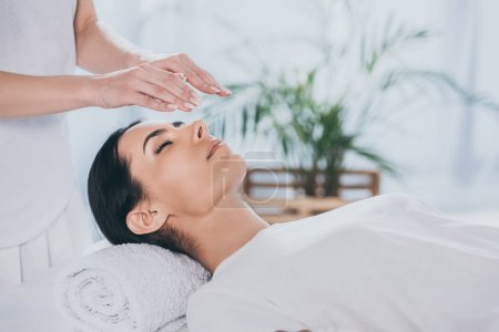 Photo for Cropped shot of calm young woman with closed eyes receiving reiki treatment above head - Royalty Free Image