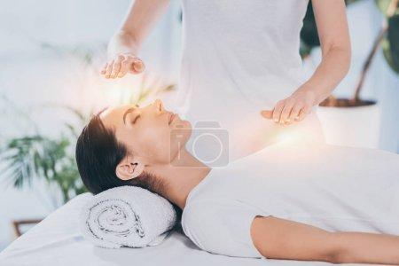 Photo pour Vue de côté de calmer la jeune femme recevant reiki thérapie sur la tête et la poitrine de guérison - image libre de droit