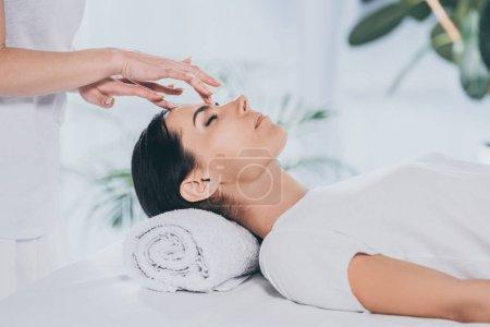 Photo pour Recadrée tir de reiki spécialiste faire thérapie curative pour calmer la jeune femme avec des yeux fermés - image libre de droit