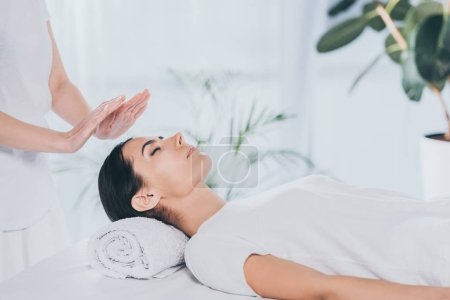 Photo for Cropped shot of peaceful young woman with closed eyes receiving reiki treatment on head - Royalty Free Image