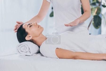 Photo pour Paisible jeune femme recevant un traitement de guérison reiki sur la tête et la poitrine - image libre de droit