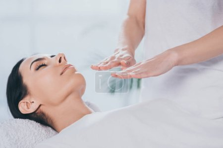 Photo for Cropped shot of peaceful young woman with closed eyes receiving healing treatment from reiki practitioner - Royalty Free Image