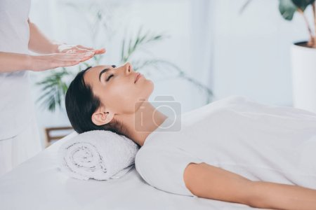 Photo for Cropped shot of peaceful young woman with closed eyes receiving reiki treatment - Royalty Free Image