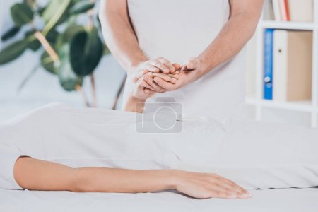 Photo for Cropped shot of reiki healer holding hand of young woman during palm healing - Royalty Free Image